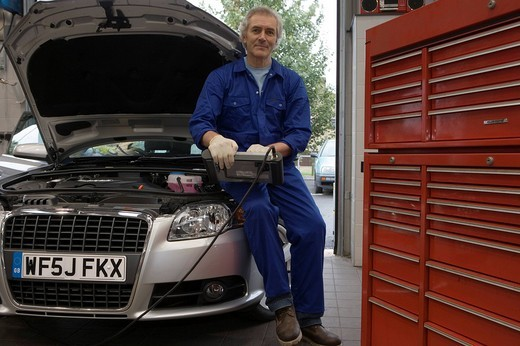 Stock Photo: 4208R-1467 Mechanic with diagnostic computer on car with open bonnet, portrait, low angle view