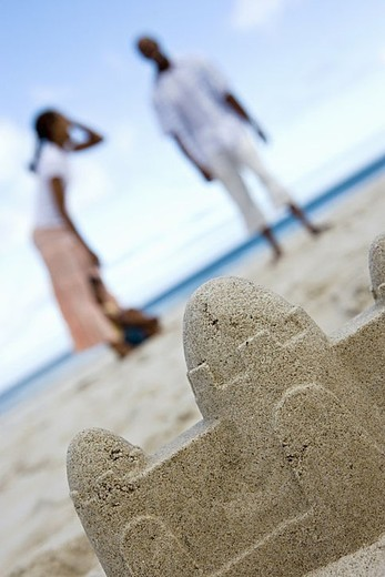 Couple standing on beach, focus on sandcastle in foreground, surface level tilt : Stock Photo