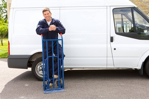 Smiling man in coveralls leaning on hand truck near work van : Stock Photo
