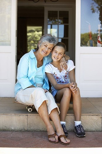 Grandmother and granddaughter 8-10 sitting on doorstep, smiling, portrait : Stock Photo