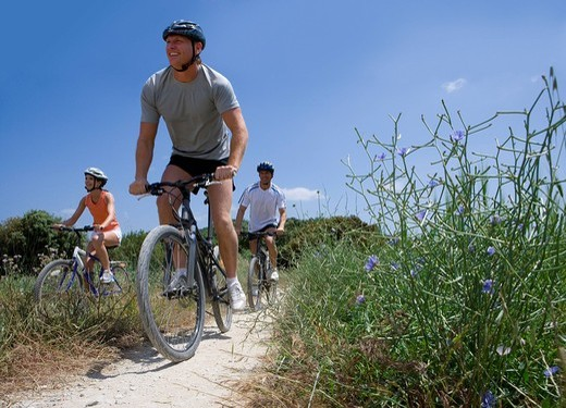 Men and woman riding bicycles on rural path : Stock Photo