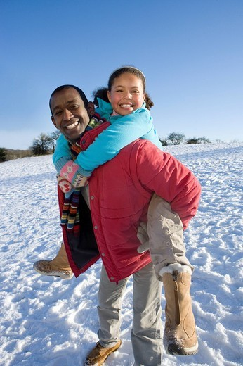 Father giving daughter piggyback ride in snowy field : Stock Photo