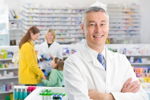 Stock Photo: 4208R-15446 Pharmacist in pharmacy with customers in background