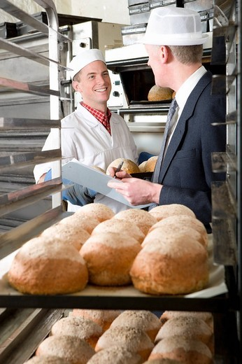 Inspector talking to baker in bakery : Stock Photo