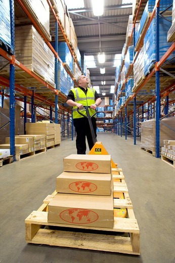 Warehouse worker with boxes on pallet truck looking up at shelves : Stock Photo