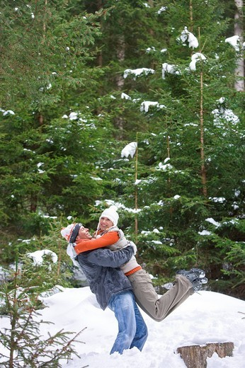 Happy couple hugging in snowy woods : Stock Photo