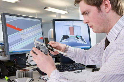 CAD designer measuring part at desk in office : Stock Photo