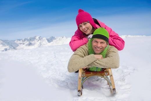 Smiling couple laying on sled on ski slope : Stock Photo