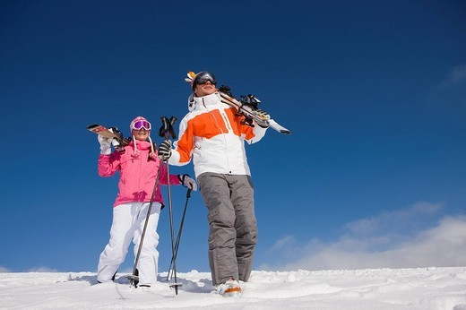 Skiers carrying skis and walking down ski slope : Stock Photo