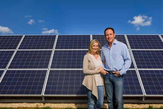 Smiling couple standing together near large solar panels : Stock Photo