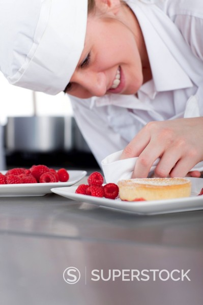 Stock Photo: 4208R-16344 Trainee chef wiping gourmet dessert in commercial kitchen