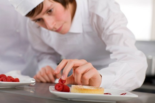 Trainee garnishing dessert in commercial kitchen : Stock Photo