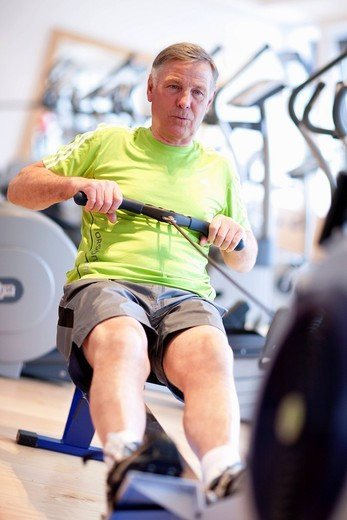Senior man exercising on rowing machine in gym : Stock Photo