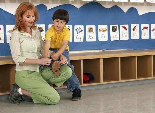 Stock Photo: 4208R-16813 Teacher tying boy´s 4-6 shoelace in classroom, alphabet cards on wall