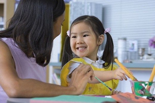 Girl 3-5 painting at desk in classroom, teacher assisting, smiling : Stock Photo