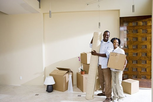 Couple moving house, standing in bare living room, woman holding box, man with rolled up carpet, portrait : Stock Photo