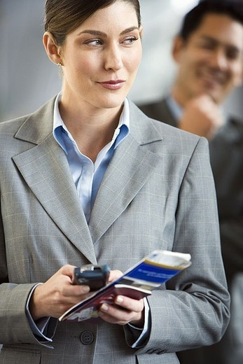 Businesswoman standing in airport terminal, holding mobile phone and ticket, making sideways glance : Stock Photo