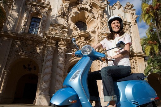 USA, California, San Diego, Balboa Park, woman riding on blue motor scooter, smiling, side view, low angle view : Stock Photo