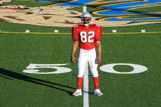 American football player, in red football strip and protective helmet, standing on pitch at 50 yard line, front view, portrait : Stock Photo