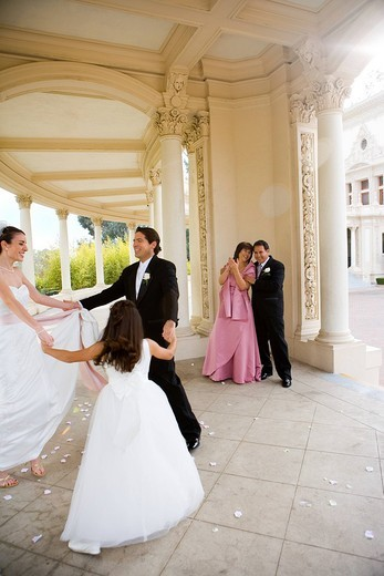 Bride and groom dancing with bridesmaid 8-10 in circle at wedding, couple looking on, smiling : Stock Photo