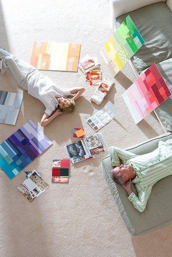 Stock Photo: 4208R-17644 Senior couple lying on floor and sofa at home, looking at colour charts, hands behind head, smiling, overhead view