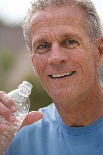 Active senior man, in blue t-shirt, drinking water from plastic bottle, smiling, close-up, portrait : Stock Photo