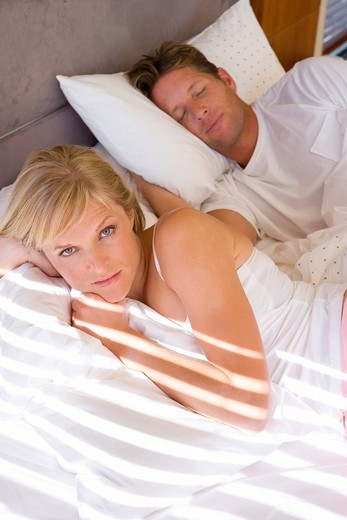 Stock Photo: 4208R-17875 Young couple lying in bed, woman in foreground, portrait