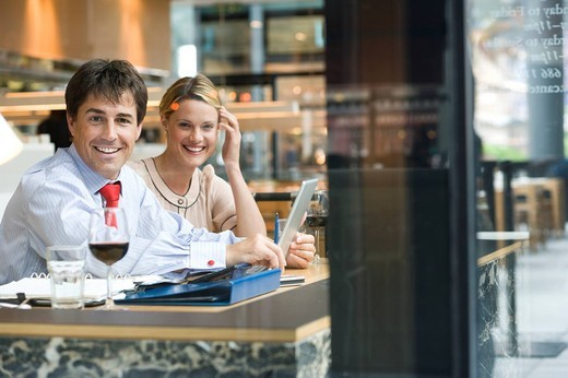 Stock Photo: 4208R-1788 Businessman and woman having drink in bar, with laptop computer, smiling, portrait