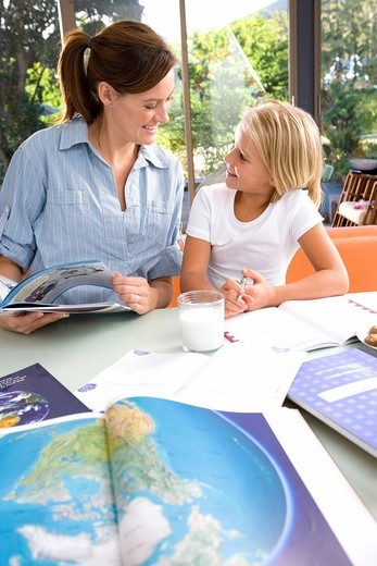 Mother helping daughter 6-8 with geography homework, world atlas in foreground : Stock Photo