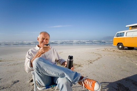 Stock Photo: 4208R-18177 Senior man in chair on beach drinking from insulated flask, camper van in background, smiling, portrait