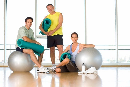 Two men and woman with exercise balls and mats in studio, portrait : Stock Photo