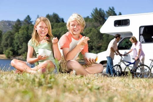 Family of four by motor home, brother and sister 8-12 eating breakfast on grass, portrait : Stock Photo