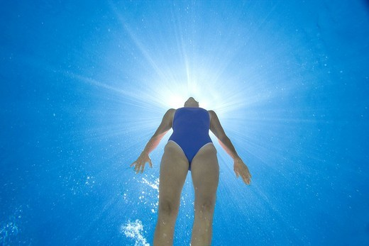 Woman in swimming pool, underwater view lens flare : Stock Photo