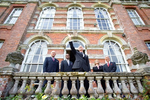Businessman by colleagues on balcony of manor house with arm raised, low angle view : Stock Photo