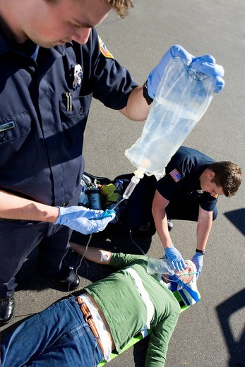 Paramedic and colleague helping man on stretcher, elevated view : Stock Photo