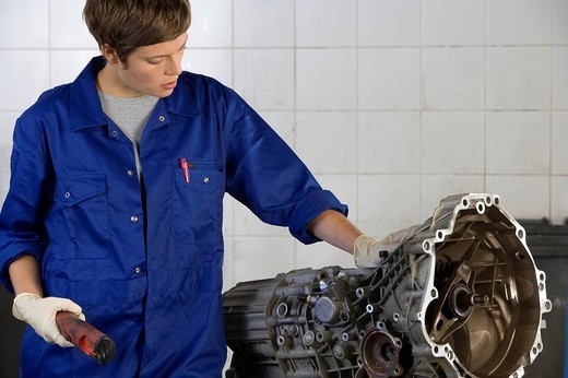 Stock Photo: 4208R-18638 Female mechanic looking at engine part