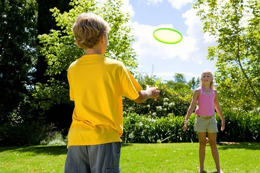 Stock Photo: 4208R-18662 Boy 9_11 and friend playing with flying disc in garden