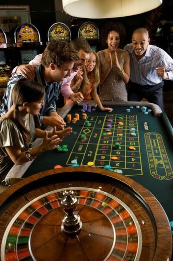 Men and women gambling at roulette table in casino, elevated view : Stock Photo