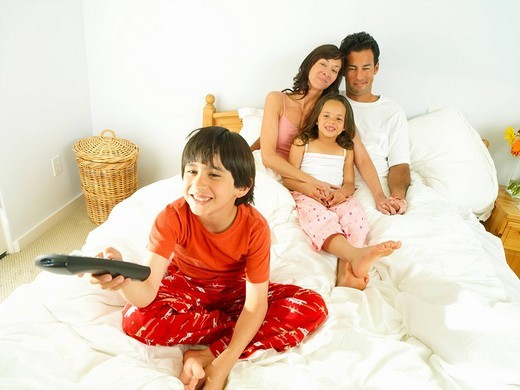 Stock Photo: 4208R-18768 Family of four in bed, boy 8-10 with remote control, smiling