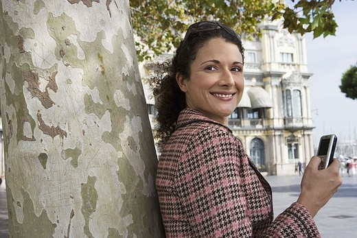 Spain, Barcelona, woman with mobile phone leaning against tree, smiling, side view, portrait : Stock Photo