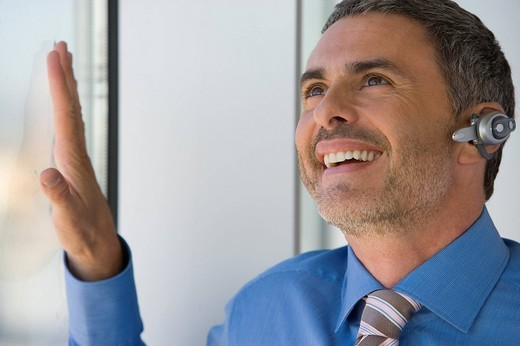 Stock Photo: 4208R-19010 Businessman with hands-free cell phone headset