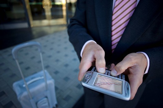 Businessman checking text messages on cell phone : Stock Photo