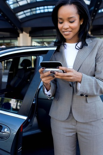 Businesswoman checking text messages on cell phone : Stock Photo