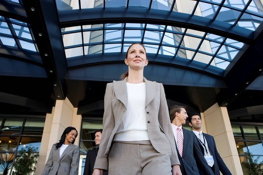 Group of business people exiting building : Stock Photo