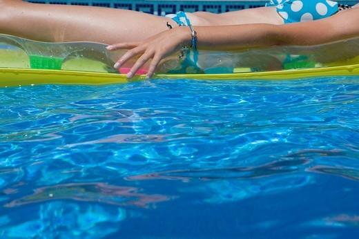 Teenage girl floating in swimming pool : Stock Photo