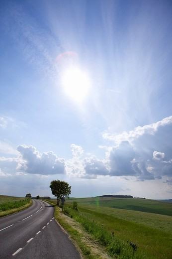 Sun shining in blue sky with clouds over countryside road : Stock Photo