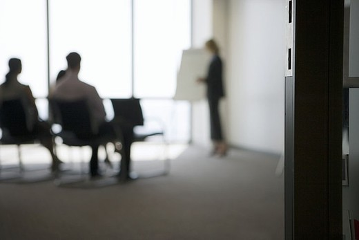 Stock Photo: 4208R-19476 Businesswoman giving presentation to colleagues in conference room, focus on doorway in foreground
