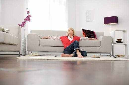 Senior woman relaxing in living room : Stock Photo