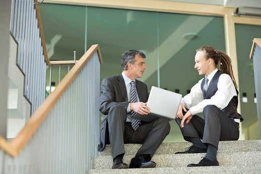 Stock Photo: 4208R-19753 Businessmen sitting at top of staircase with laptop