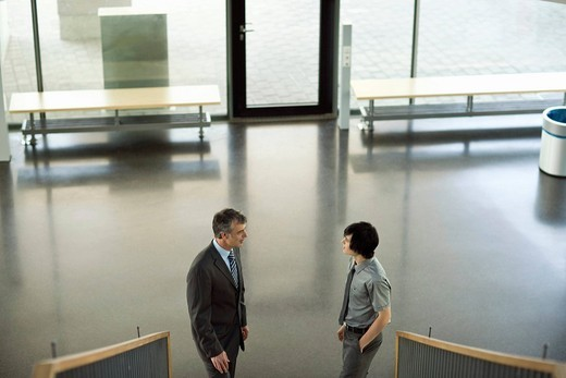 Businessmen standing at bottom of staircase having discussion : Stock Photo